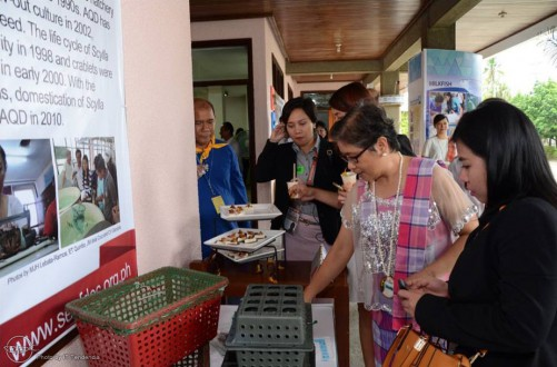 APEC delegates sampling on crispy fried soft-shell crab while Dr. Emilia Quinitio explains the culture of soft-shell crabs in individual plastic boxes